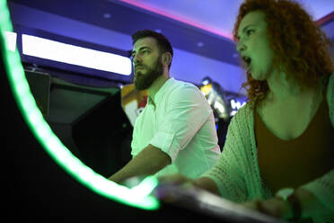 Couple playing at gaming machine in an amusement arcade - ZEDF02573