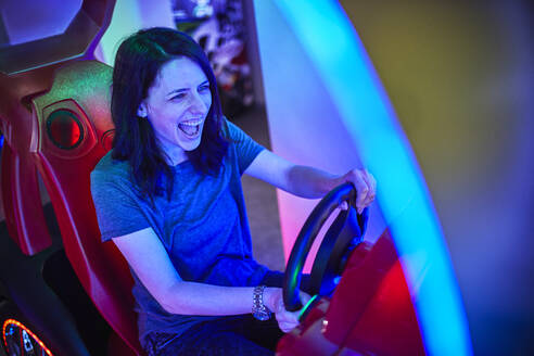 Excited woman playing and having fun with a driving simulator in an amusement arcade - ZEDF02585