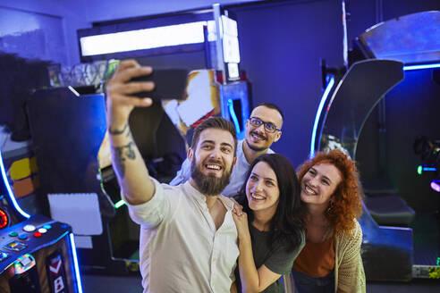 Happy friends taking a selfie in an amusement arcade - ZEDF02591