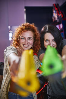 Happy friends playing and shooting with pistols in an amusement arcade - ZEDF02600