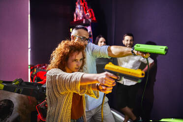 Friends playing and shooting with pistols in an amusement arcade - ZEDF02603