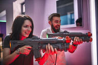 Happy couple playing and shooting with rifles in an amusement arcade - ZEDF02606