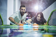 Happy couple playing air hockey and having fun in an amusement arcade - ZEDF02612