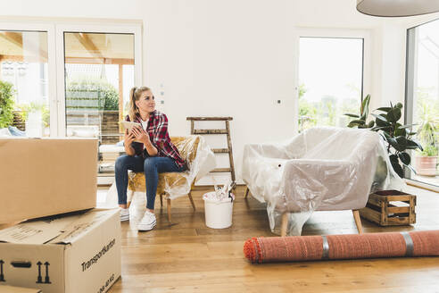 Woman moving into new home using tablet - UUF18854