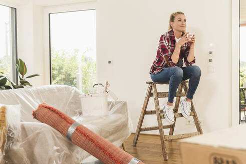 Woman moving into new home having a coffee break - UUF18863