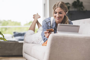 Smiling woman on couch with credit card and tablet - UUF18944
