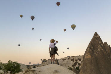 Young woman and hot air ballons, Goreme, Cappadocia, Turkey - KNTF03314