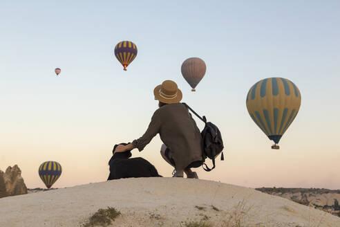 Young woman and hot air ballons, Goreme, Cappadocia, Turkey - KNTF03317