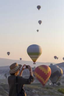 Young woman and hot air ballons, Goreme, Cappadocia, Turkey - KNTF03323