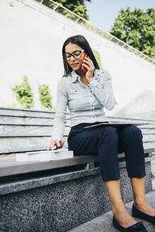 Young businesswoman sitting on a bench talking on cell phone and taking notes - OYF00033