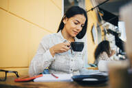 Smiling young woman drinking coffee in a cafe - OYF00045