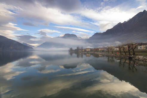 Mountains and village are reflected in Lake Mezzola at dawn shrouded by mist, Verceia, Chiavenna Valley, Lombardy, Italy, Europe - RHPLF07473