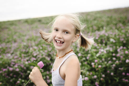 Laughing girl holding clover flowers - EYAF00397