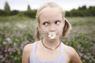 Girl with chamomile flower in her mouth - EYAF00403
