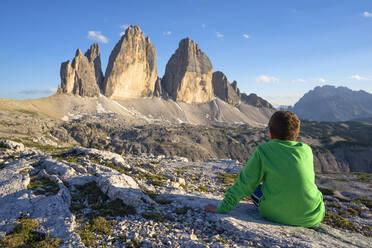 Rear view of boy looking at Tre Cime Di Lavaredo against sky, Veneto, Italy - LOMF00887