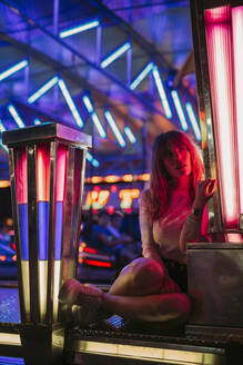 Young woman sitting at the bumper car on a funfair at night - LJF00878