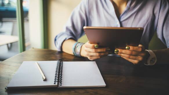 Woman sitting in a cafe using a digital tablet - OYF00052