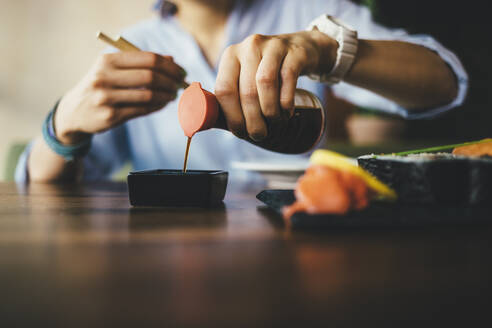 Close-up of a woman eating sushi in a restaurant - OYF00058