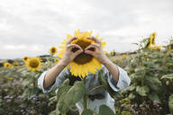 Playful boy covering his face with sunflower in a field - KMKF01054