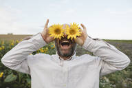 Playful man covering his eyes with sunflowers in a field - KMKF01057