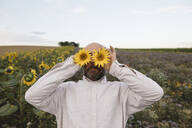 Playful man covering his eyes with sunflowers in a field - KMKF01060