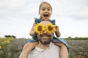 Sunflowers covering eyes of playful man with daughter in a field - KMKF01063