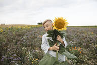 Portrait of a boy holding a sunflower in a field - KMKF01066