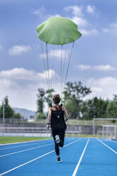 Female runner with parachute on tartan track - STSF02204