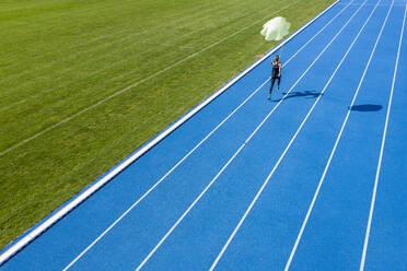 Female runner with parachute on tartan track - STSF02207