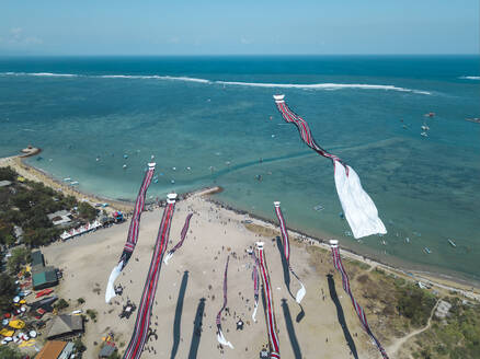 Aerial view of kites flying at beach against blue sky during festival in Bali, Indonesia - KNTF03339