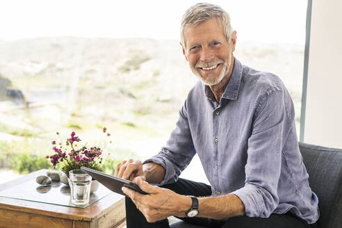 Portrait of smiling senior man using tablet at home - SBOF01989