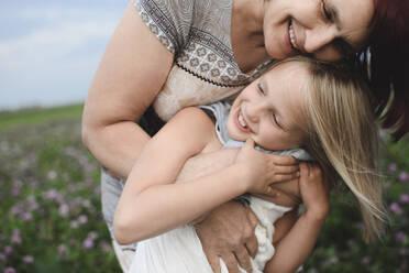 Happy grandmother hugging granddaughter on flower meadow - EYAF00421