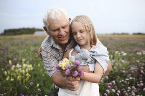 Portrait of grandfather and granddaughter with picked flowers on a meadow - EYAF00424