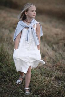 Portrait of blond little girl wearing white summerdress walking on a meadow - EYAF00433