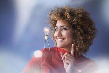 Portrait of smart woman with lightbulb on her shoulder - KSHSF00006