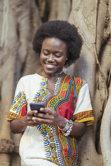 Smiling young woman leaning on a tree trunk using her smartphone - DLTSF00019