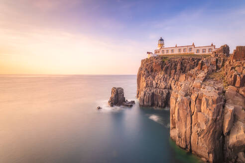 Neist Point Lighthouse by sea during sunset, Waterstein, Isle of Skye, Highlands, Scotland, UK - SMAF01429