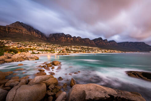 Long exposure at sunset at Camps Bay with cloud over Table Mountain and the Twelve Apostles, Cape Town, South Africa, Africa - RHPLF07879