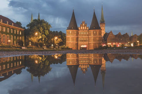 Holstentor by Trave River against cloudy sky at dusk, Lübeck, Germany - KEBF01321