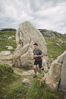 Trail runner in coastal landscape, Ferrol, Spain - RAEF02279