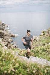 Trail runner on stairs in coastal landscape, Ferrol, Spain - RAEF02288