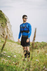 Trail runner standing in nature, Ferrol, Spain - RAEF02291