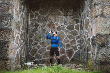 Trail runner standing at a wall drinking water - RAEF02297