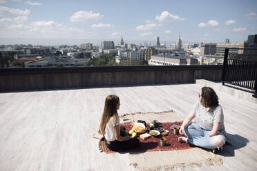Woman with below-elbow amputation and girl having a healthy meal on the roof - EYAF00450