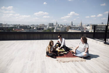 Woman with below-elbow amputation having a healthy meal on the roof with woman and girl - EYAF00453
