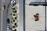 Aerial view of three people having a meal on the roof - EYAF00456
