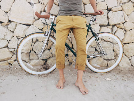 Barefoot man with Fixie bike in front of natural stone wall on the beach, partial view - DLTSF00043