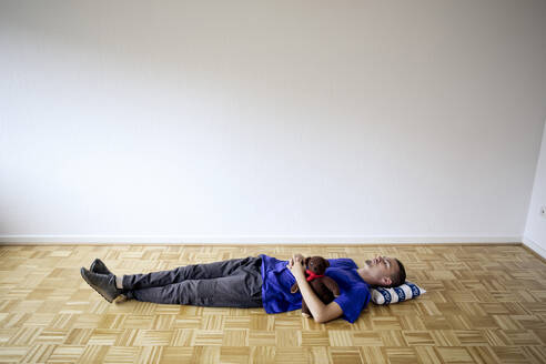 Young man laying on the floor in an empty apartment embracing a teddy bear - FLLF00287