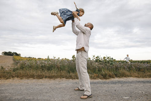 Father playing with his daughter, holding her aloft - KMKF01075