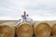 Father and his children sitting on hay bales, watching sky - KMKF01078